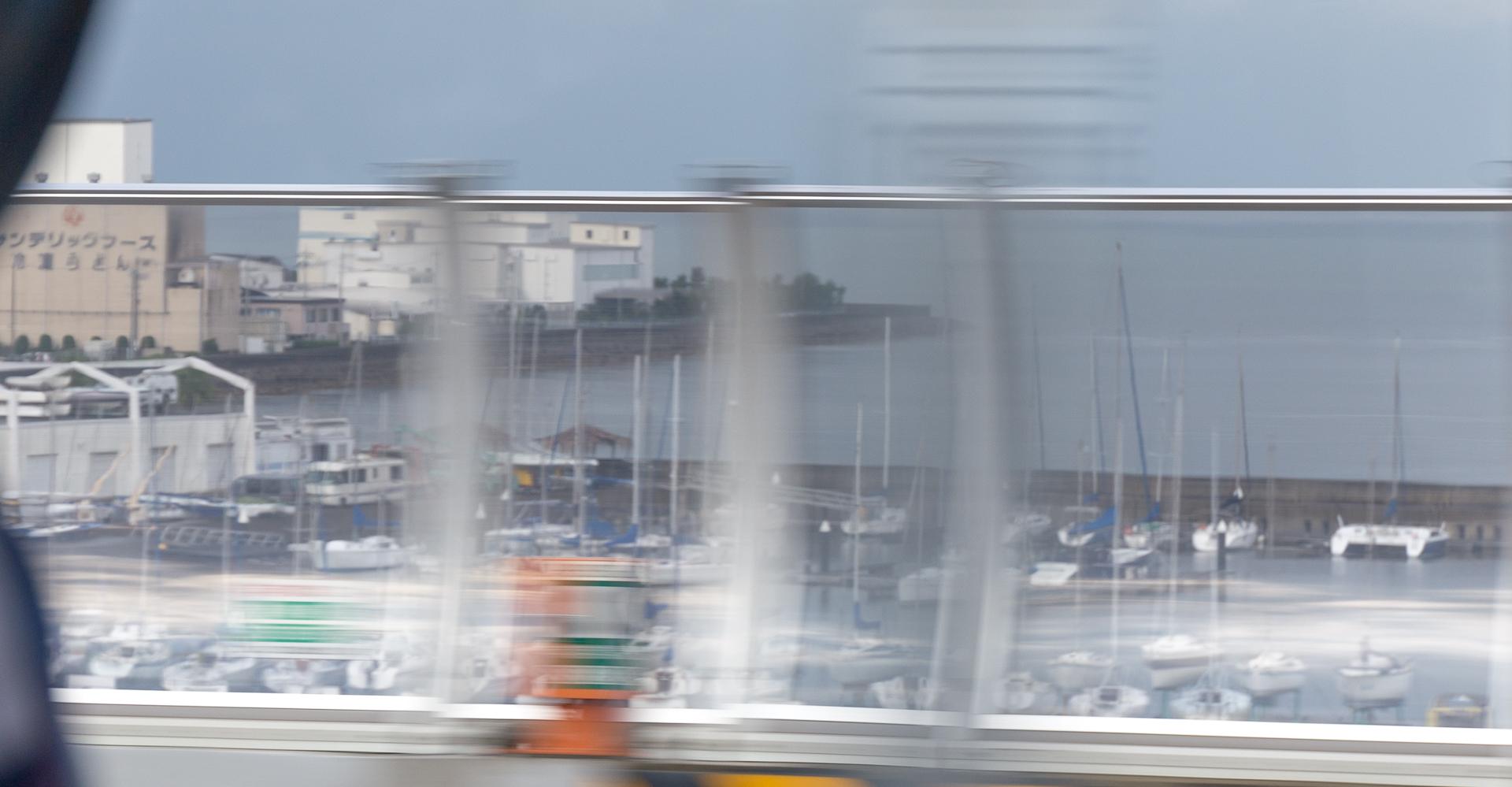 Endnu en lystbådehavn, nu med lystbåde. Igen taget igennem vinduet på en bus og med et stakit der står i vejen